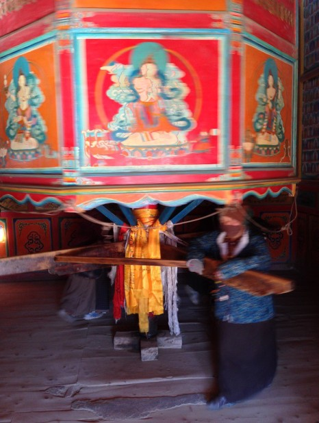 Old Tibetans are rotating a prayer wheel